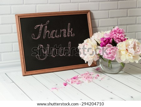 Beautiful bouquet of pink and white peonies in the glass vase with petals and black chalkboard with inscription Thank You on the light grey brick and wood background. - stock photo