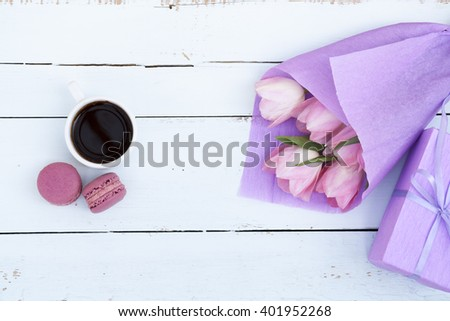 Beautiful bouquet of pink tulips in violet paper, gift, cup of coffee and two pink macaroons on light wooden background - stock photo