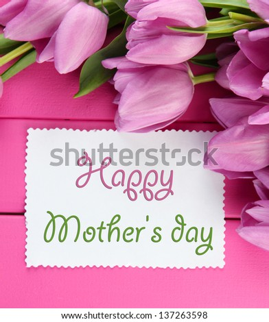 Beautiful bouquet of purple tulips and blank card on pink wooden background - stock photo