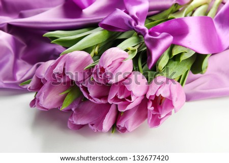 Beautiful bouquet of purple tulips on satin cloth, isolated on white - stock photo