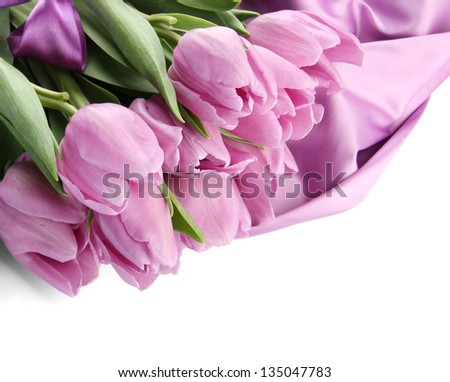 Beautiful bouquet of purple tulips on satin cloth, isolated on white