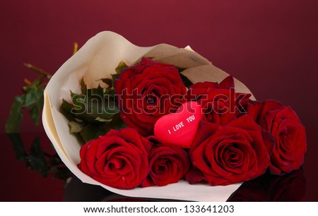 Beautiful bouquet of red roses with valentine on red background