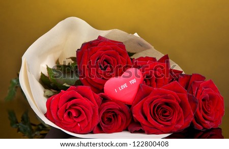 Beautiful bouquet of red roses with valentine on yellow background