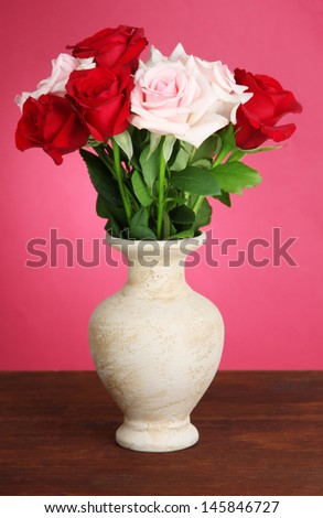 Beautiful bouquet of roses in vase with gift on table on pink background