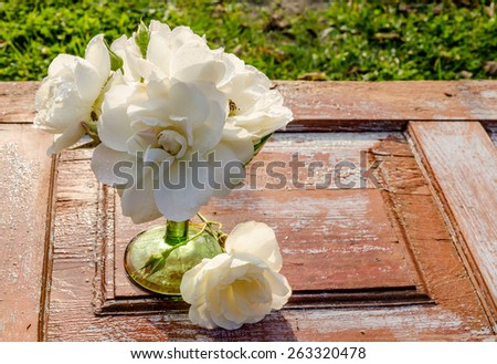 Beautiful bouquet of roses with drops in green glass vase on old wooden table. After the rain. Rustic style. - stock photo