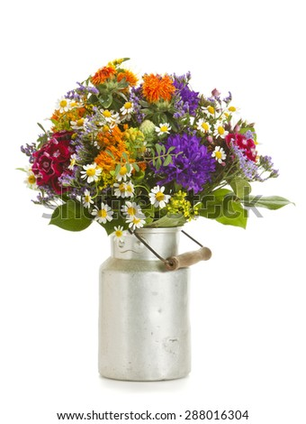 Beautiful bouquet of summer flowers in old milk canister isolated on white - stock photo