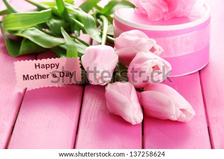 Beautiful bouquet of tulips and gift for Mother's Day on pink wooden background - stock photo