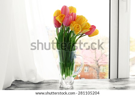 Beautiful bouquet of tulips in carafe on windowsill