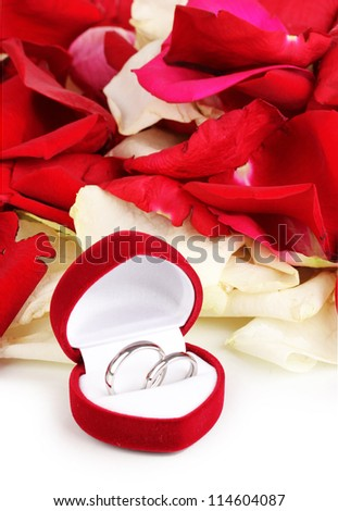 Beautiful box with wedding rings on red, white and pink rose petals background isolated on white