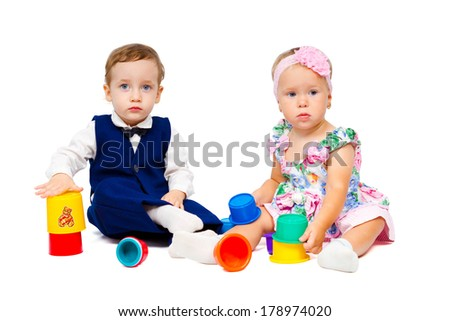 Beautiful boy and girl playing together. Charming children build multi-colored pyramid isolated on white background - stock photo