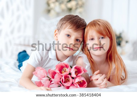 beautiful boy and girl with tulips lying on the floor, Mother's Day, 8 March, a happy birthday - stock photo