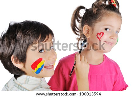 Beautiful boy painting his sisters face - stock photo