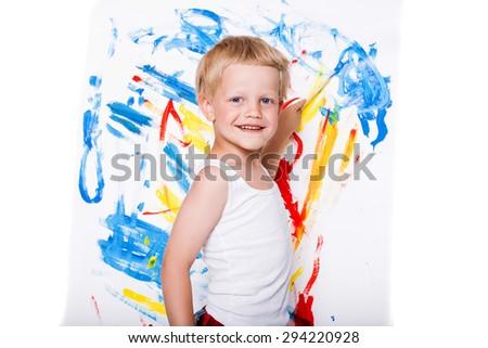 Beautiful boy painting with paintbrush on canvas. Education. Creativity. Studio portrait over white background - stock photo