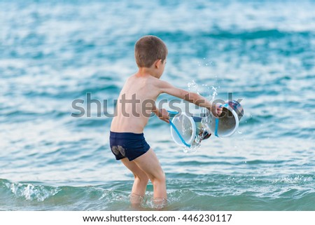 Beautiful boy playing with toys  at the seaside