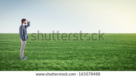 Beautiful boy stand on meadow and looks ahead - stock photo