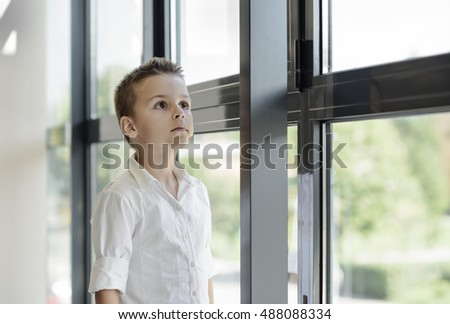 beautiful boy standing next to a window high-rise building