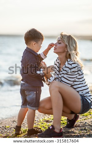 Beautiful boy with a woman relaxing on the beach. Throw pebbles into the sea, running, jumping, laughing and having a great time with each other at sunset. - stock photo