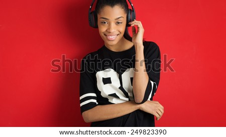 Beautiful brazilian teenager with headphones against red background. - stock photo