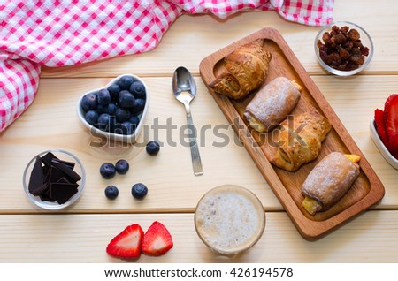 Beautiful  breakfast. Glass cup of coffee with milk served with crushed chocolate, different pastries, berries and raisins on the wooden background. Top view. - stock photo