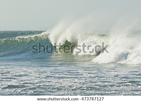 beautiful breaking wave with sea spray on a windy afternoon