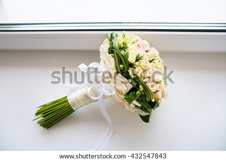 beautiful bridal bouquet of roses lying on the windowsill