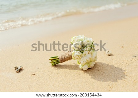 Beautiful bridal bouquet of white lotuses and orchids on a tropical beach. - stock photo