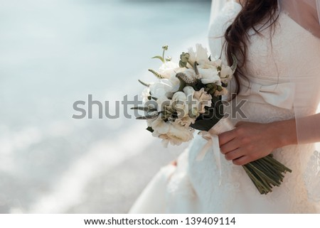 beautiful bridal bouquet of white roses in the hands of the bride - stock photo
