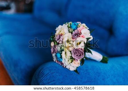 Beautiful bridal bouquet on blue sofa armrest. Wedding concept - stock photo