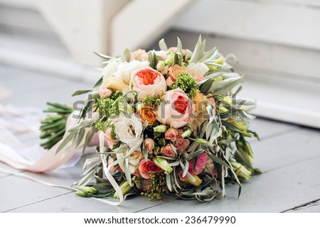 Beautiful bridal bouquet tied with silk ribbons and lace with a key in the form of heart. Roses and branches of an olive tree on the old vintage background . Wedding Accessories - stock photo