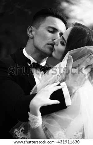 Beautiful bridal couple of young man embracing and kissing pretty woman outdoor, black and white