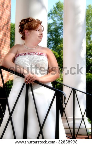 Beautiful bride along a rail going up some steps.  Captured while looking away from the camera and a soft focus lens used to add an elegance to the portrait. - stock photo