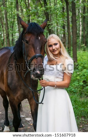 Beautiful bride and a horse in the forest