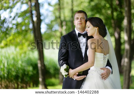 Beautiful bride and groom by a tree - stock photo