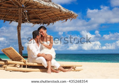 Beautiful bride and groom having fun and kissing at sandy tropical beach on sunbed under umbrella, romantic vacation. Beach wedding concept - stock photo