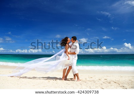 Beautiful bride and groom having fun and kissing on white sand tropical beach. Beach weding