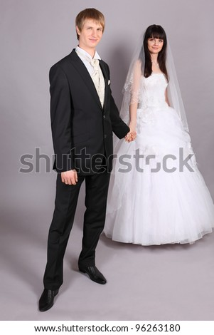 Beautiful bride and groom hold hands and stand in studio on gray background; bride stands behind groom; focus on man - stock photo