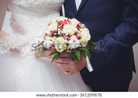 Beautiful bride and groom holding a bouquet of flowers