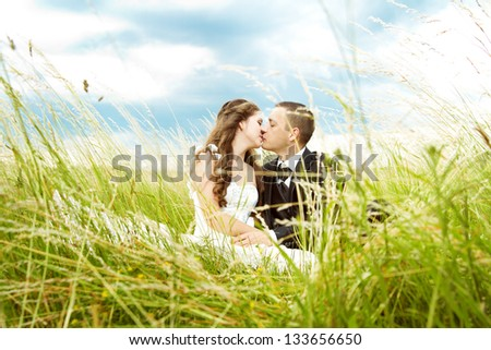Beautiful bride and groom  kissing in grass.  Wedding couple outdoors - stock photo