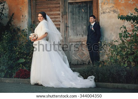 beautiful bride and groom near the wall and trees