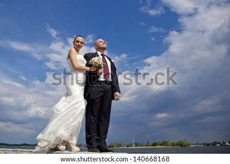 beautiful bride and groom on the background of clouds
