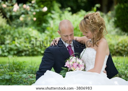 Beautiful bride and groom sitting together in the garden