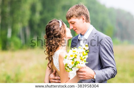 Beautiful bride and groom standing in grass and kissing. Wedding couple - stock photo