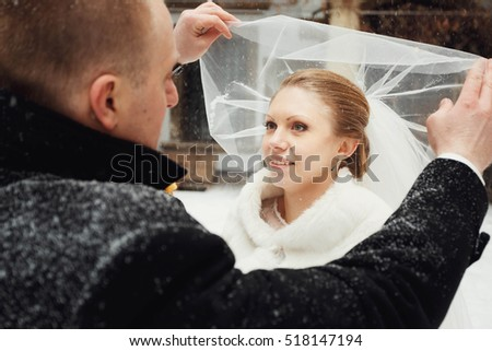 Beautiful bride and groom standing on a snowy street