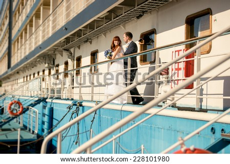 Beautiful bride and groom standing on cruise ship deck at sunset - stock photo