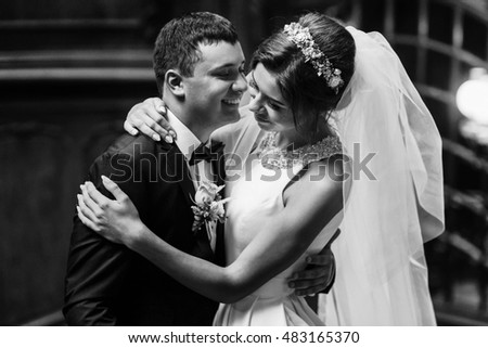 Beautiful bride and groom standing together and hugging indoors