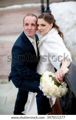 beautiful bride and manful groom in winter snow
