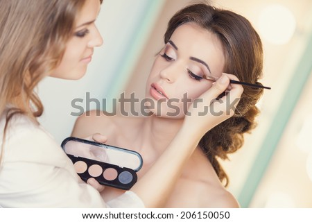 Beautiful bride applying wedding make-up by professional make-up artist on the wedding day - stock photo