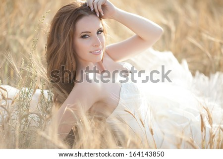 Beautiful bride at wedding day outdoor. Attractive newlywed woman in wedding dress. Portrait of bride. - stock photo