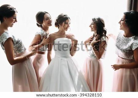 Beautiful bride & bridesmaids posing near window, wedding preparation - stock photo
