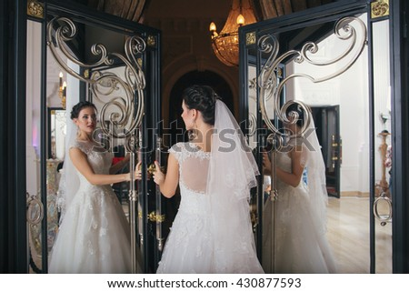 beautiful bride brunette girl in white wedding dress with hairstyle and bright makeup looks in the mirror